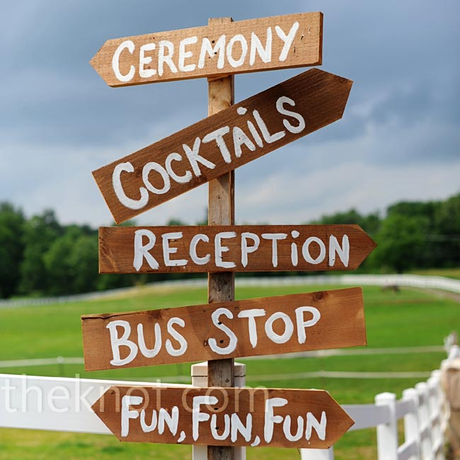 A wooden sign pointed guests to everything at the wedding, from the ceremony to the bus stop and cocktails.