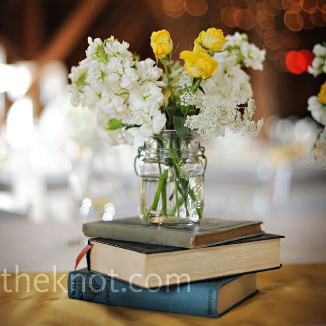 Clear and aqua Mason jars filled with Queen Anne's lace, mini carnations and yellow spray roses rested on the tables and atop antique books.