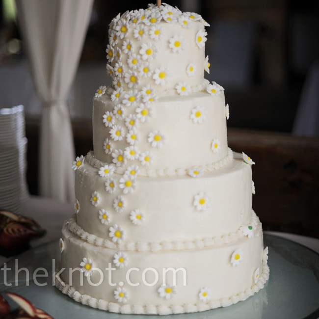Mini sugar daisies cascaded down the four-tiered white buttercream cake.