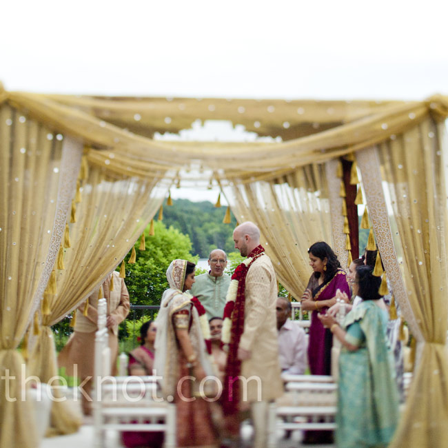 Both ceremonies took place outside facing the water. For the Indian ceremony, the couple stood beneath a sparkly, gold-draped canopy (called a mandap).