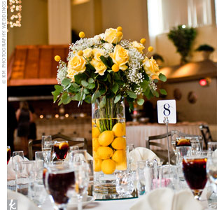 For the head table, the couple opted for a tall vase filled with submerged lemons and topped with an arrangement of roses.