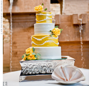 Fresh yellow roses and pearl-shaped piping decorated the four-tiered yellow and white cake.