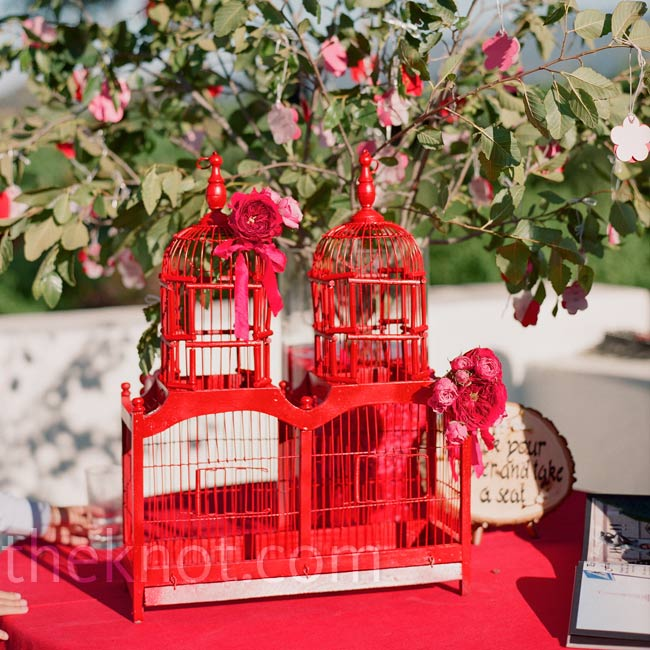 Tiny cards shaped like cherry blossoms hung from a tree for guests to take. A red birdcage added a vintage touch to the table.