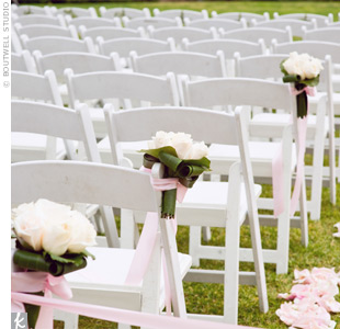Nosegay bouquets of all-white flowers were tied to chairs along the ceremony aisle with pink ribbon.