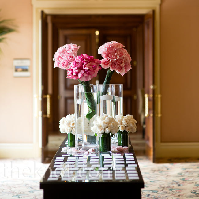 For a modern display, the cards were laid flat on a wooden table with pink and white monobotanical flower arrangements and floating candles.