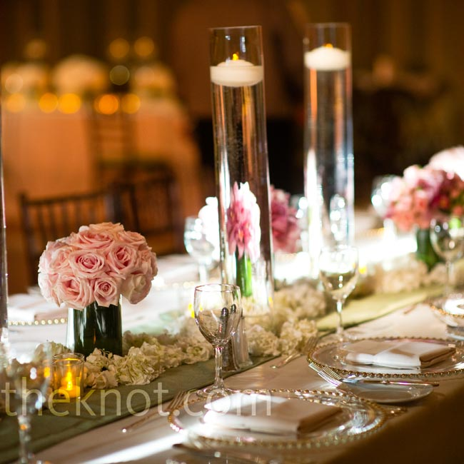 Low monochromatic arrangements and floating candles set in tall cylinder vases were dotted down the long banquet tables at the reception.