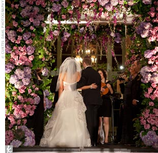 Amy and Evan stood beneath a flower-packed huppah. Even more flowers set on tall candelabras lined the ceremony aisle.