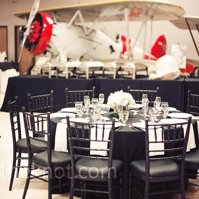 Black linens and chairs coordinated with the various WWII aircraft surrounding the dance floor and tables.