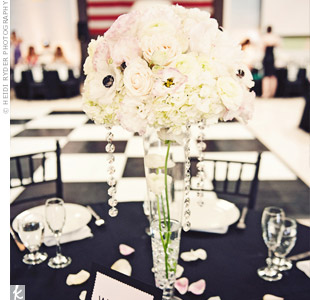 Arrangements of white peonies, hydrangeas, roses and anemones, accented with hanging crystals, topped the dinner tables.