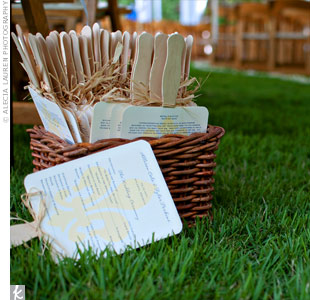 To help keep guests cool during the outdoor ceremony, the couple provided fan programs that were displayed in wicker baskets at the end of the aisle.