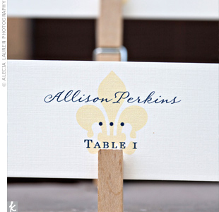 Escort cards decorated with a yellow fleur de lis were attached by clothespins to a wooden rack.