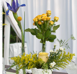 Free-form arrangements of irises, roses and craspedia in an assortment of clear and milk-glass vases had a just-picked look.