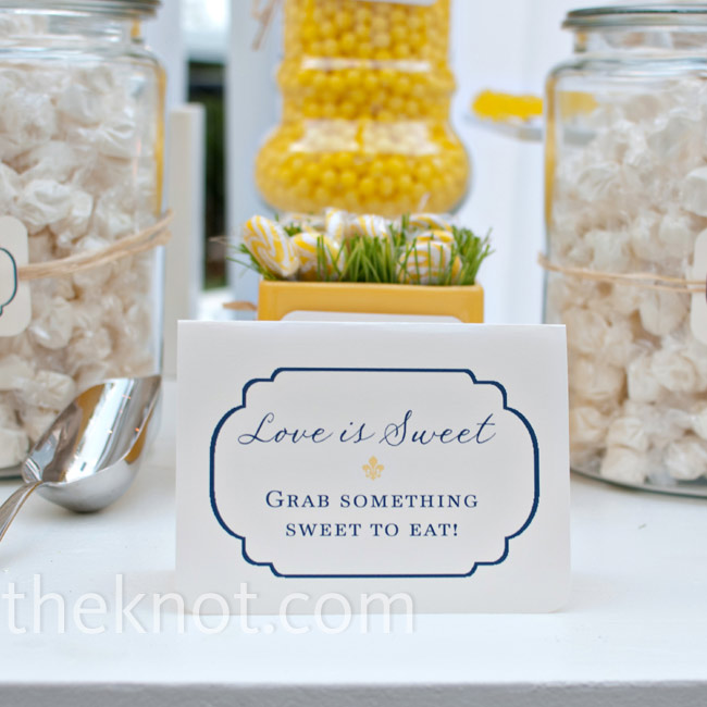 Jars of yellow and white candy were labeled with navy and yellow tags attached with raffia.