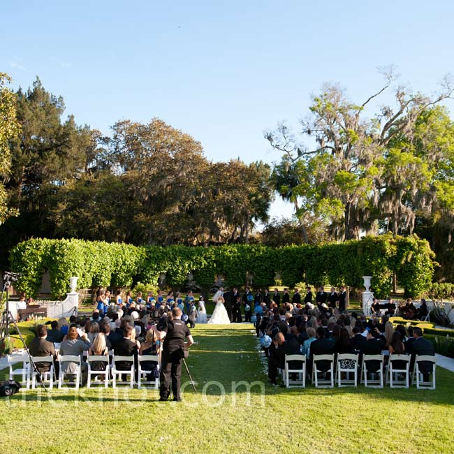 The ceremony was held in the sunken garden at Crane Cottage, framed by arched boxwoods and trees covered in Spanish moss.