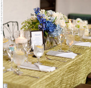 A grouping of blue and white hydrangeas and roses in a rectangular vase set off the textured green table linens.