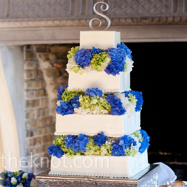 A silver monogram topped the buttercream cake while fresh blooms were tucked between each of the four tiers.