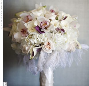 Creamy Vendela and Snowy Jewel roses, hydrangeas and orchids were framed with a collar of soft feathers and wrapped in ivory satin ribbon.