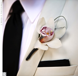 A cream orchid with a pale purple center was accented with a small loop of grass for a simple yet elegant boutonniere.