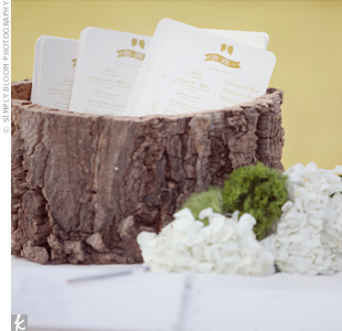 White programs with the couple's silhouettes were placed in a hollow tree trunk for a natural look.