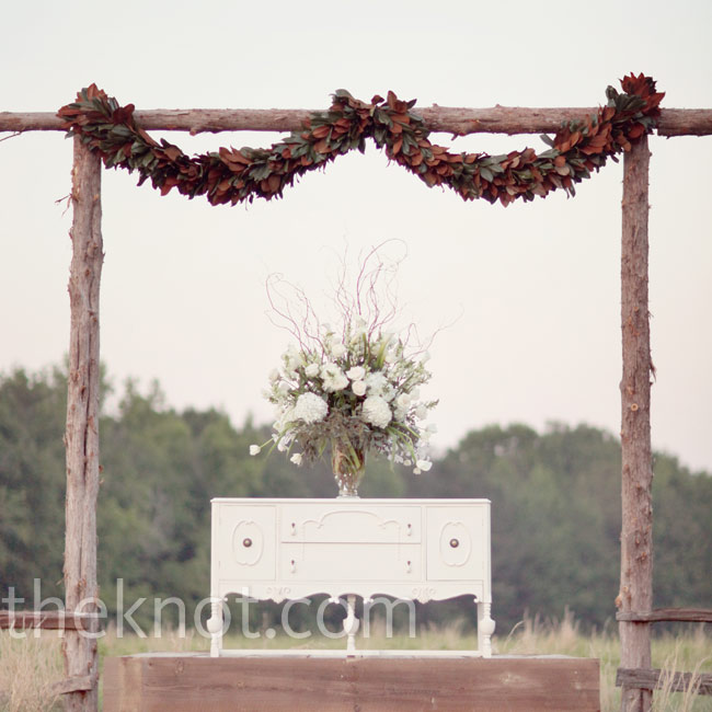 Kemble and Ashley's father created the ceremony backdrop with wood gathered from the farm. A vintage dresser topped with flowers and curly willow served both as a focal point and a makeshift altar.