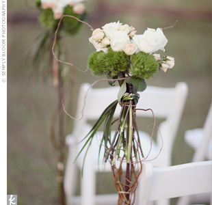 Organic clusters of white, peach and green blooms were tied together with grasses and placed along the aisle.