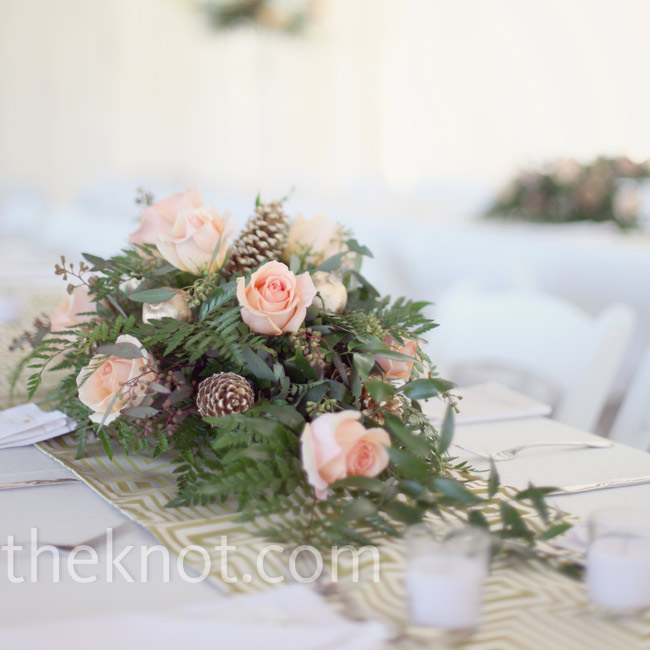 Low centerpieces overflowed with ferns, pink roses and pinecones for a fresh, just-gathered look.