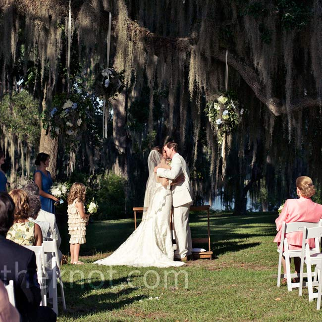 Three kissing balls of hydrangeas and moss hung from an oak tree during the ceremony.