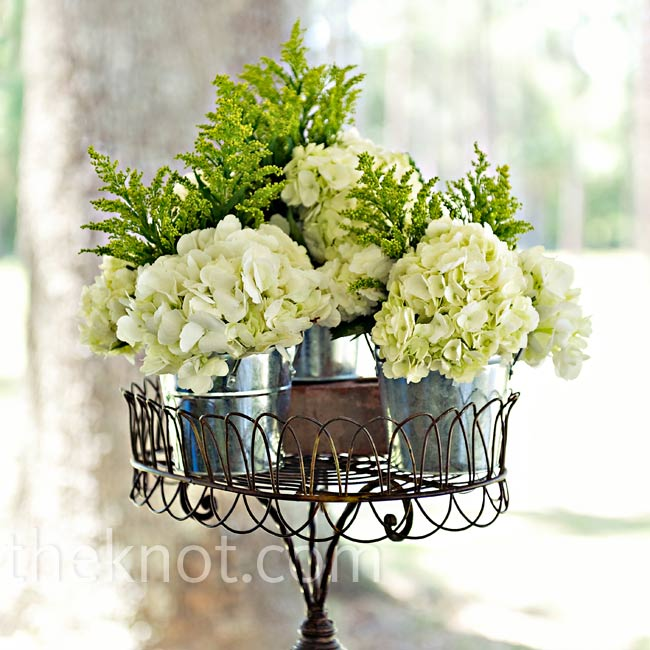 Green and white hydrangeas and soft ferns were placed in an antique planter.