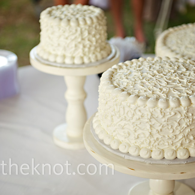 Instead of one large cake, the couple served three cakes decorated in lacy patterns and displayed on wooden stands created by the bride's grandparents.