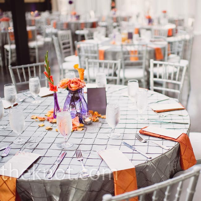 Platinum pintuck linens and chiavari chairs were given added drama with tangerine napkins and colorful blooms tucked in purple vases