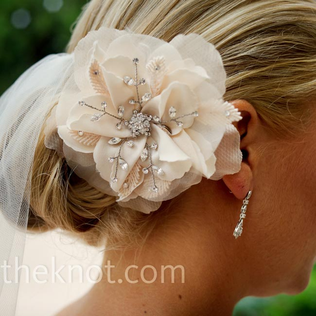 For a clean, polished look, Katie wore her hair pulled back in a chignon with a Swarovski-embellished fabric flower.
