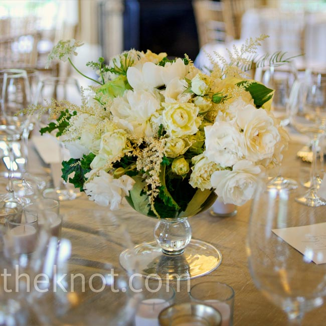 Low glass urns filled with white and green peonies, astilbe, lady's mantle and garden roses topped the tables.