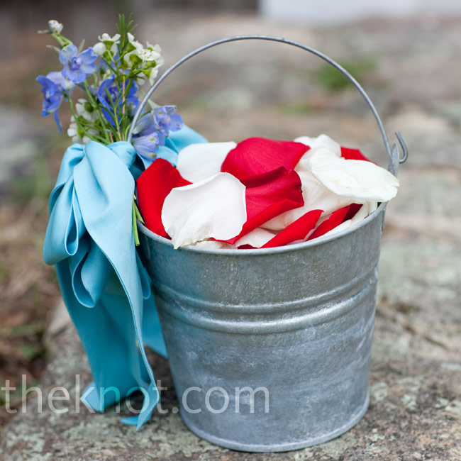 Brian's niece carried a pail of rose petals tied with blue fabric from Jenn's mom's wedding dress.