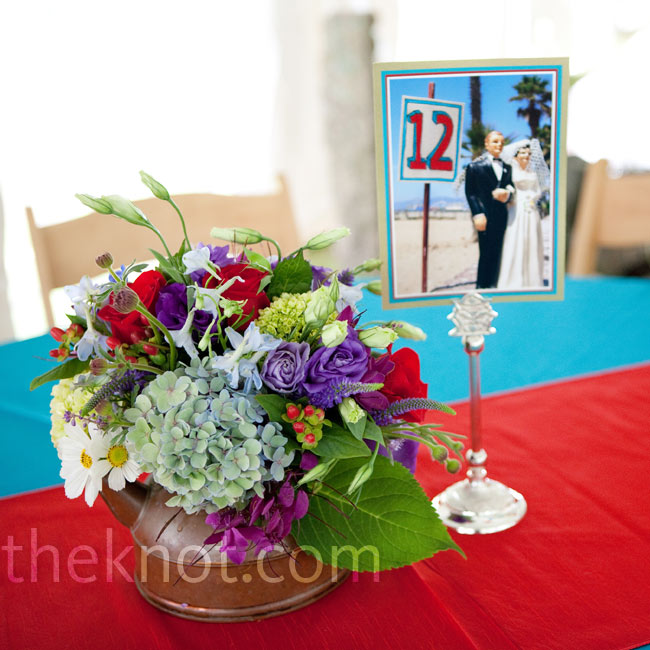 Colorful, mixed flowers were set in brass teapots.