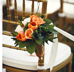 Small arrangements of orange tulips and roses hung from the aisle chairs.