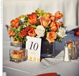 Orange roses, celosia and tulips in clear cube vases served as low centerpieces.