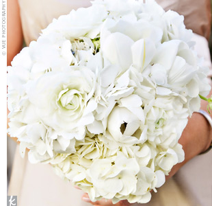 Bridesmaids carried white hydrangeas, tulips and ranunculus tied with ribbon.