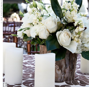Rustic birch vessels were filled with ivory stock, roses, tulips and magnolia leaves for the centerpieces.