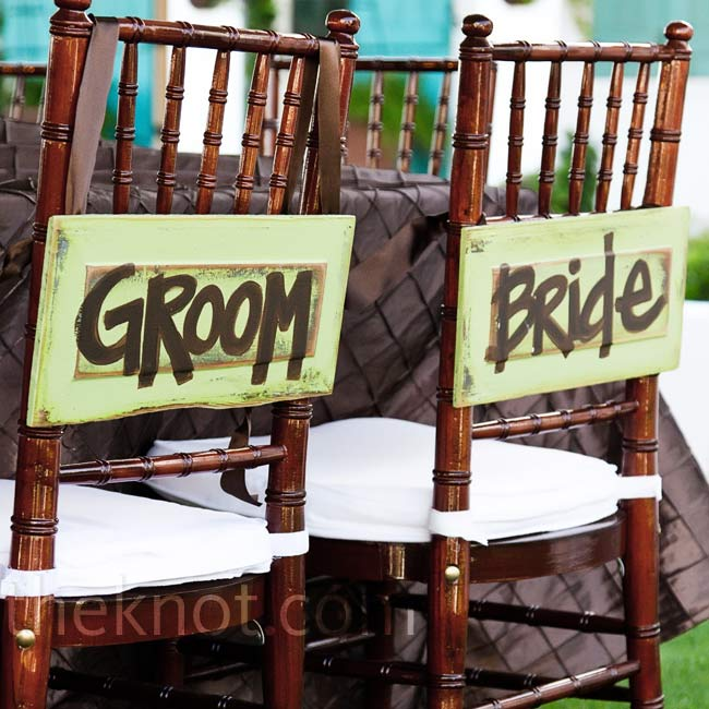 Mahogany chiavari chairs were adorned with painted signs at the reception.