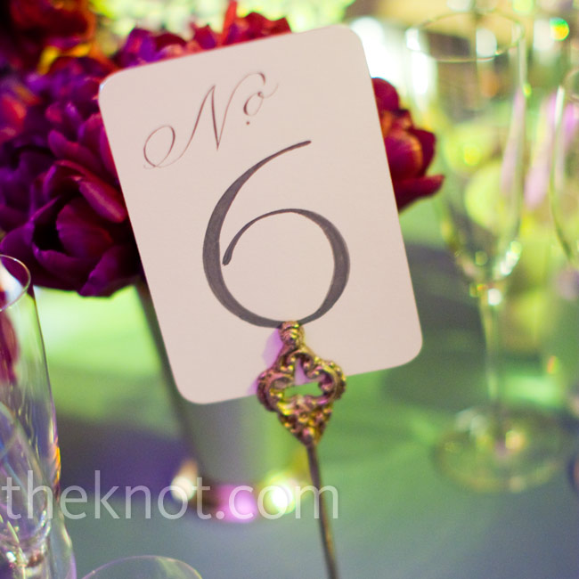 The couple's calligrapher wrote out table numbers onto cards and then clipped them onto silver stands.
