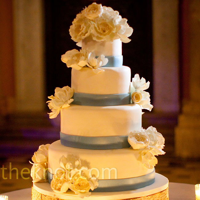 Fondant ribbons bordered the four-tiered cake, which was accented with sugar flowers.