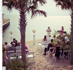 Jacqueline and Wick married on the beach of the Currituck Sound. Wooden pedestals topped with arrangements of white hydrangeas marked the altar space.