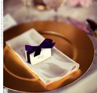 Sophisticated gold chargers were topped with a box of gourmet chocolates tied in dark purple ribbon.