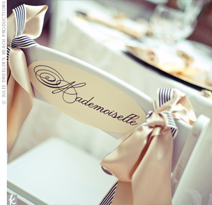 The bride and groom's chairs were decorated with Monsieur and Mademoiselle signs tied with a combination of striped grosgrain and champagne satin ribbon.