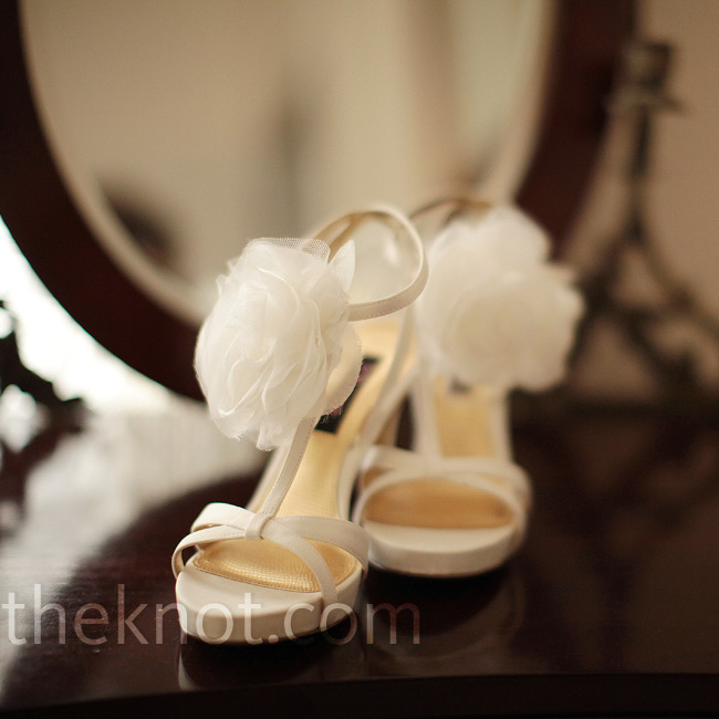 Bethany wore soft ivory T-strap heels adorned with white chiffon flowers for a touch of playfulness.