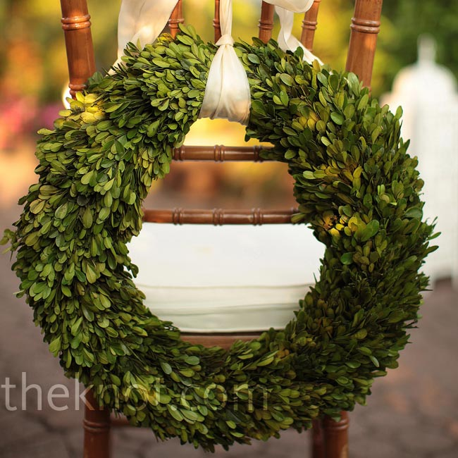 Wreaths of greenery were suspended by an ivory ribbon from the bride and groom's chairs.