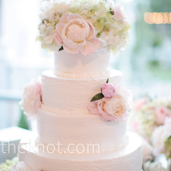 Peonies and hydrangeas adorned the white buttercream cake which had a subtle wood grain pattern on its four tiers.