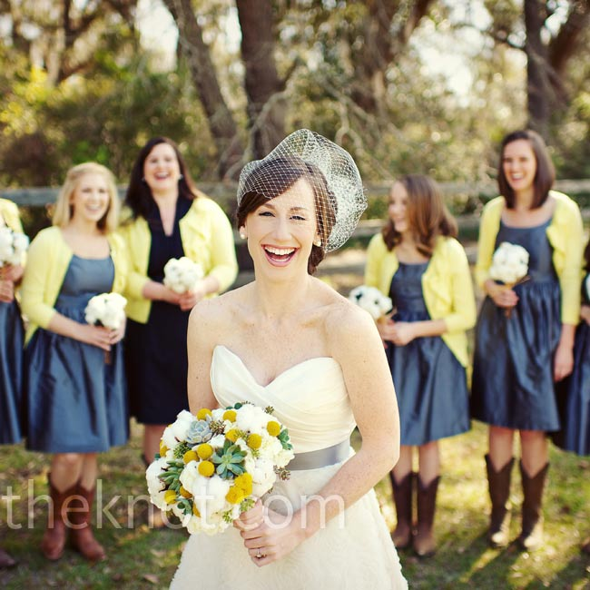 A cage veil accented Bonnie's A-line gown and sweetheart neckline. Her bridesmaids paired their gray silk shantung dresses with yellow cardigans and cowboy boots for a casual look.