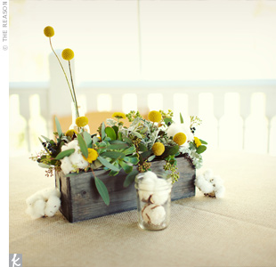 Succulents, craspedia and cotton were arranged in rustic wooden containers and placed on burlap overlays.