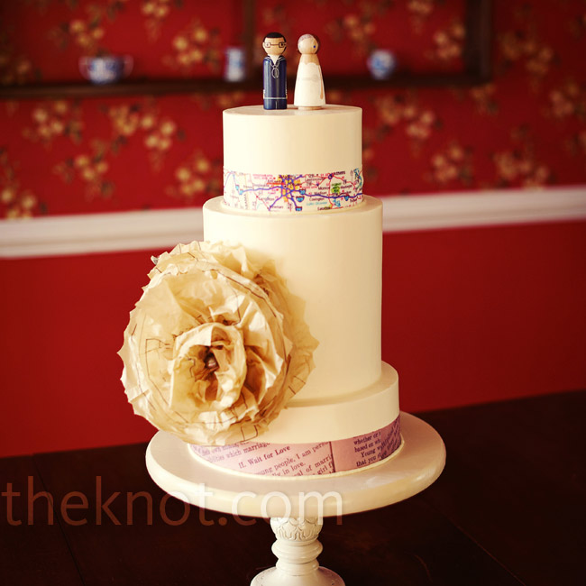 The three-tiered buttercream cake was decorated with a paper flower and paper bands around the tiers while a wooden hand-painted bride and groom perched on top.